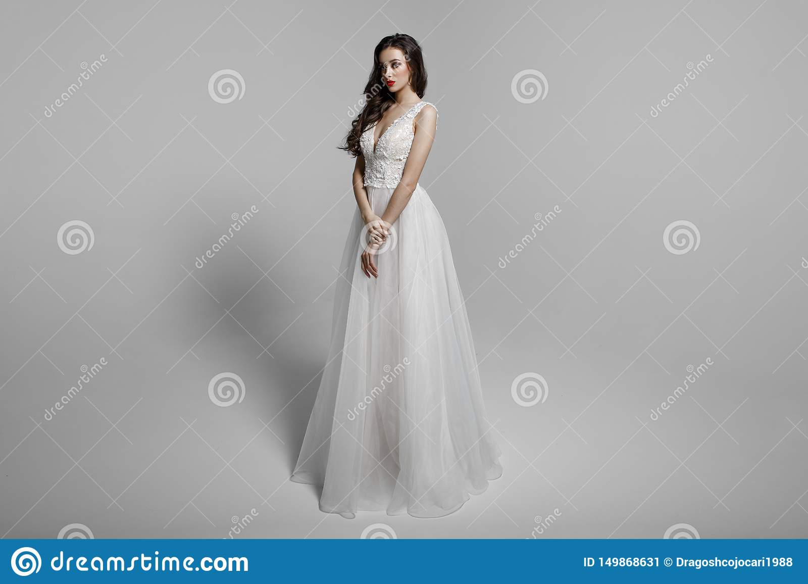 Young woman in beautiful dress sitting in studio. Attractive caucasian model, isolated on a white background.