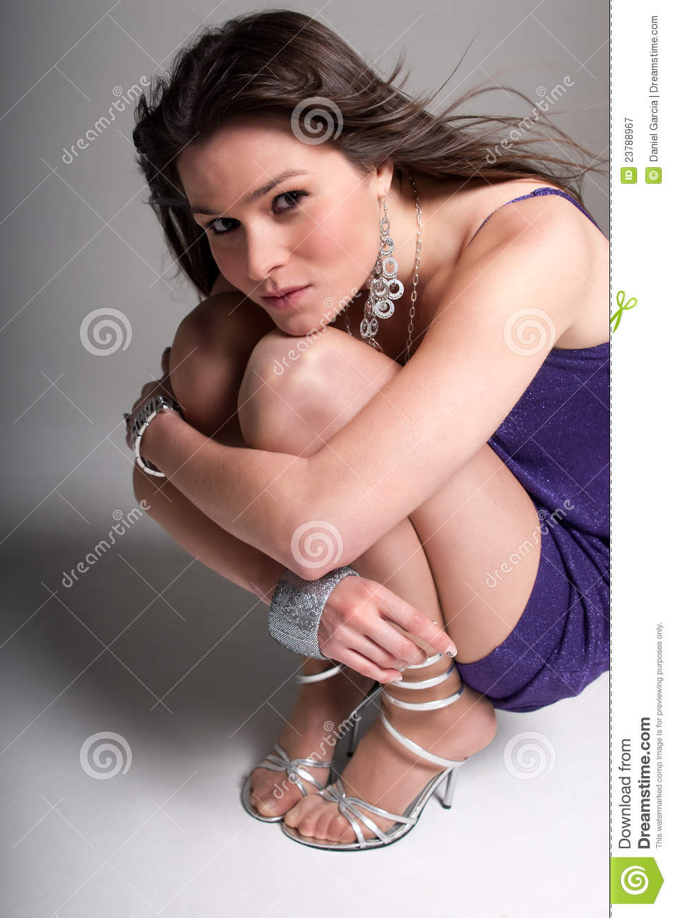 Young woman beauty fashion pose crouched over grey