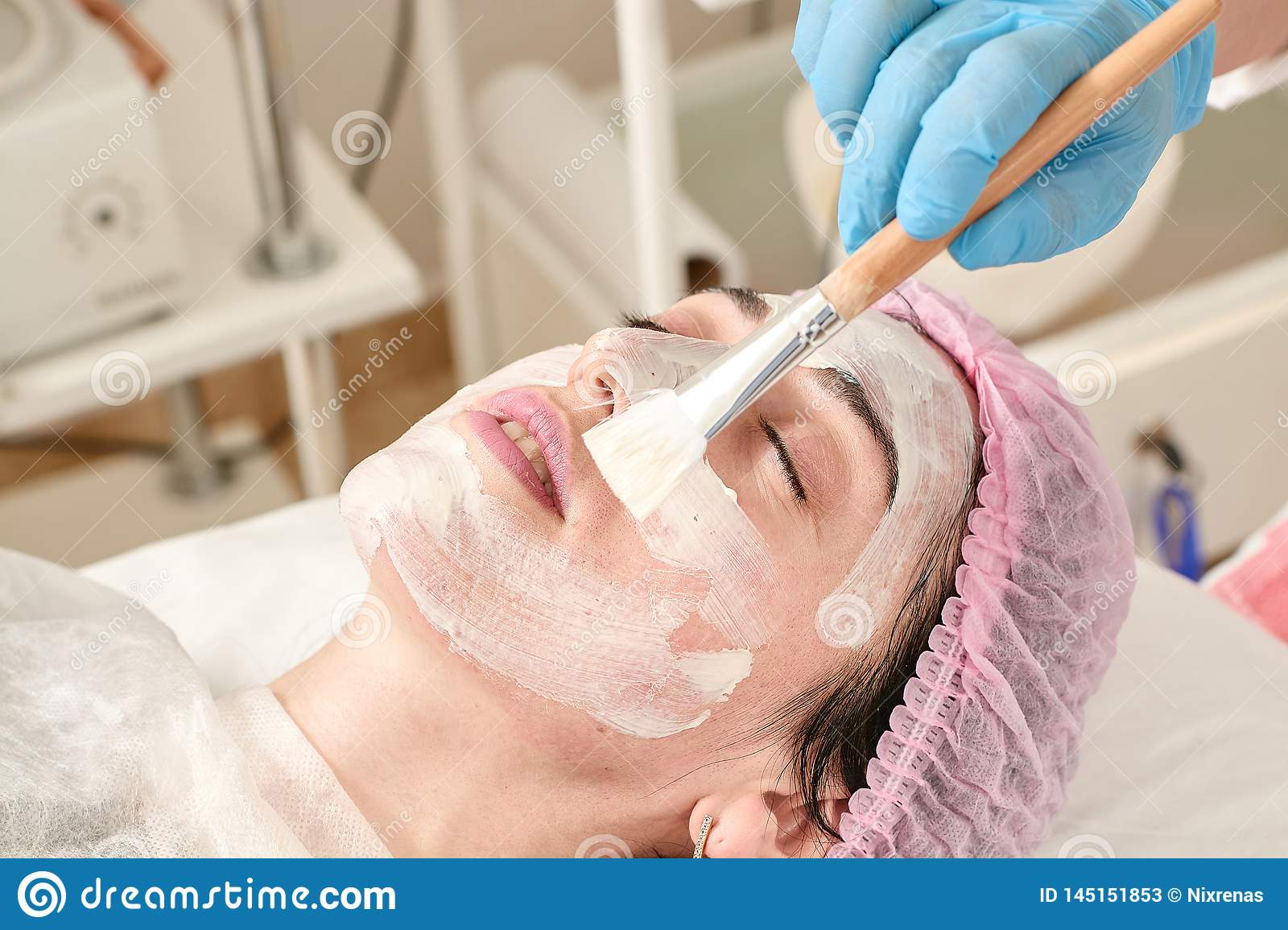 Young woman in beauty salon does make application of moisturizing, softening, regenerating mask