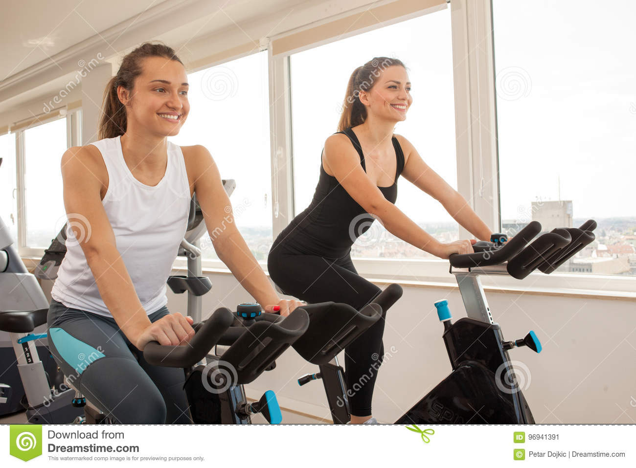 Young woman biking in the gym, exercising legs doing cardio wor