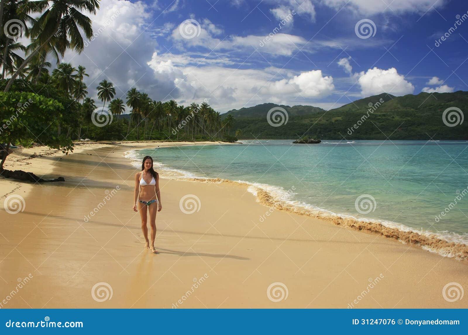 Young woman in bikini walking at Rincon beach, Samana peninsula