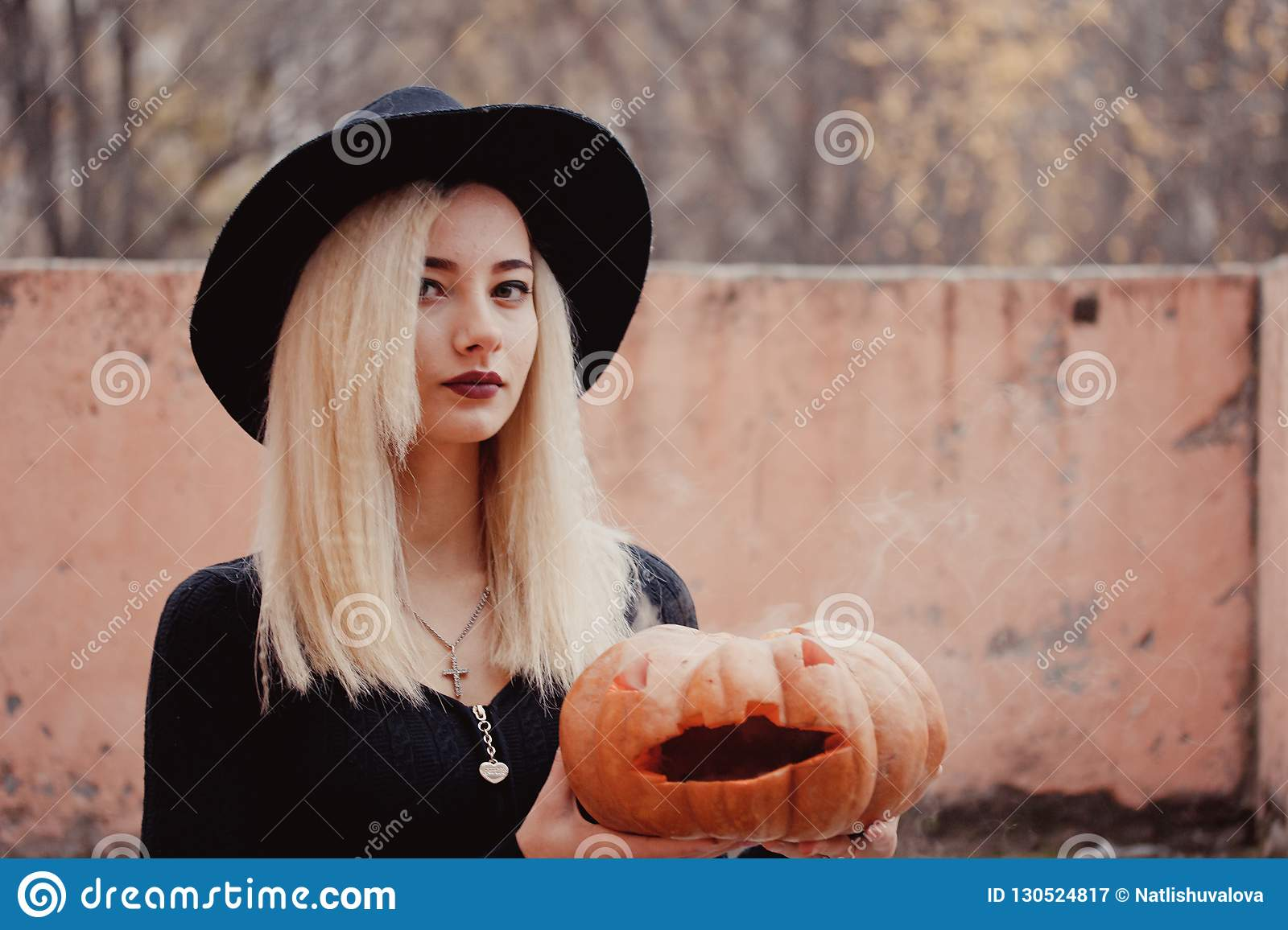 Young woman in the black coat holding the halloween pumpkin with the white smoke coming from inside of it in the autumn