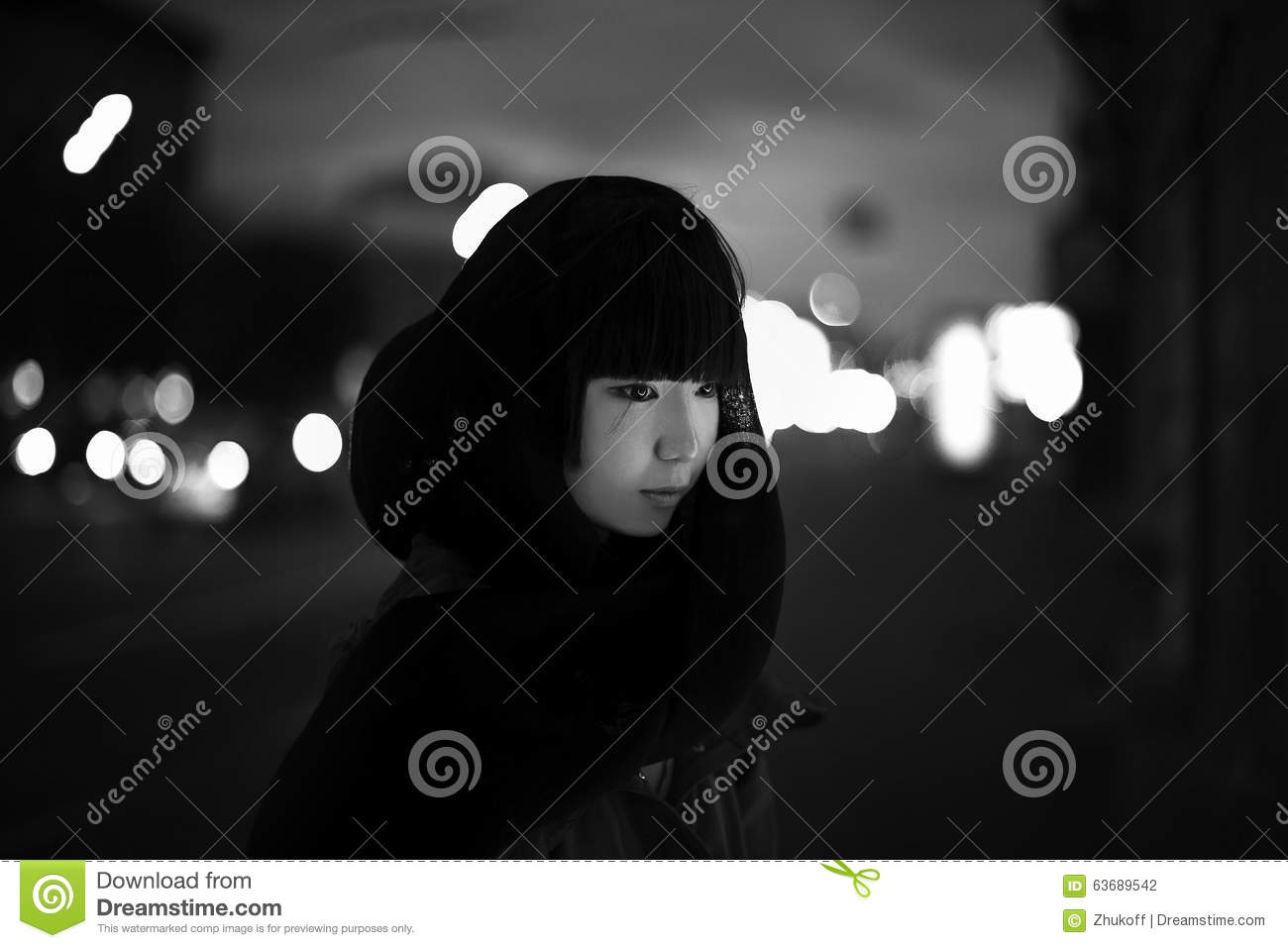 Young woman in black coat at the night street