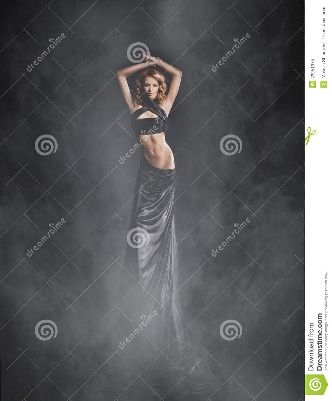 A young woman in a black dress on a foggy background