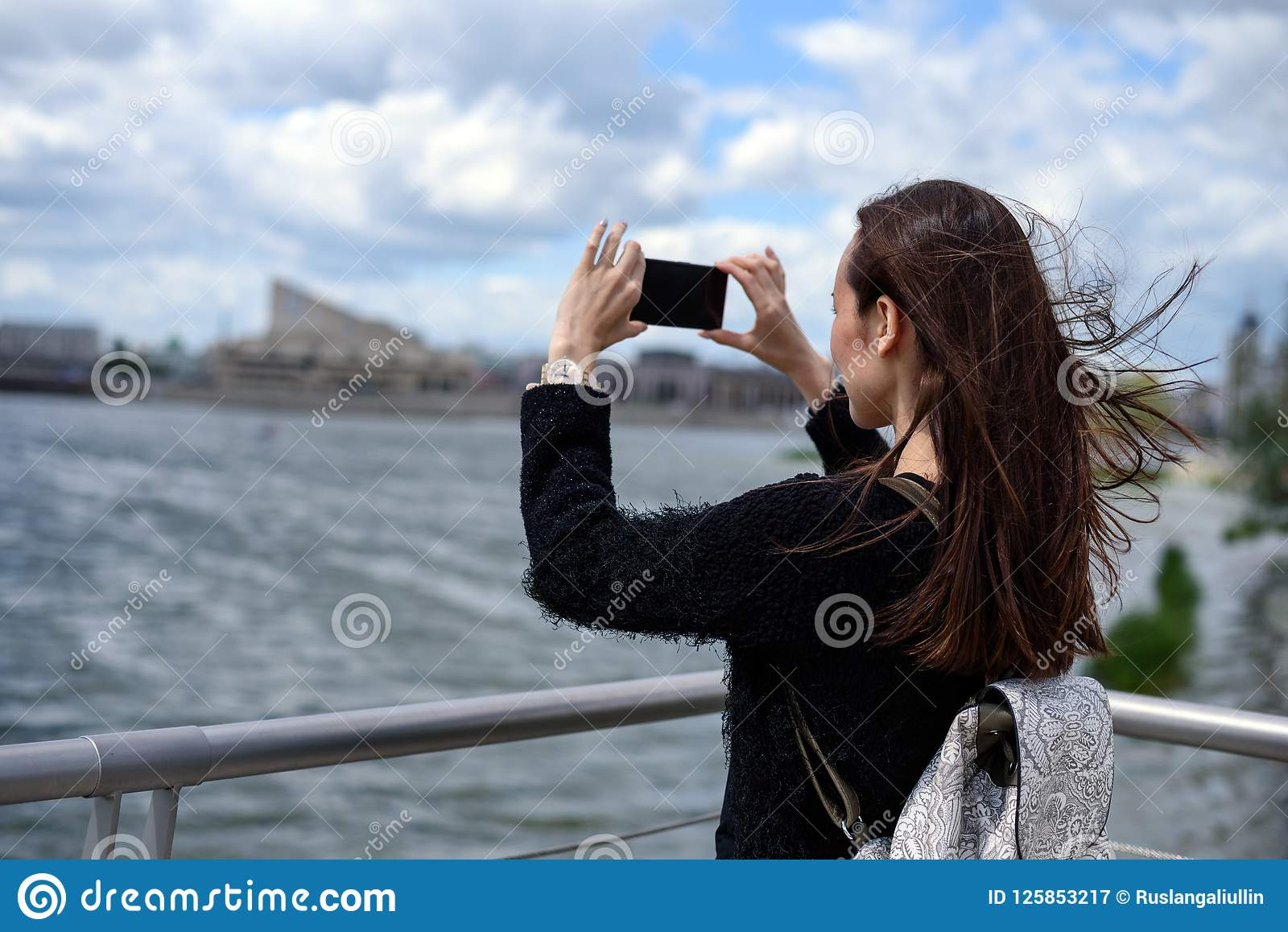 Young woman on the waterfront taking pictures of the city landscape