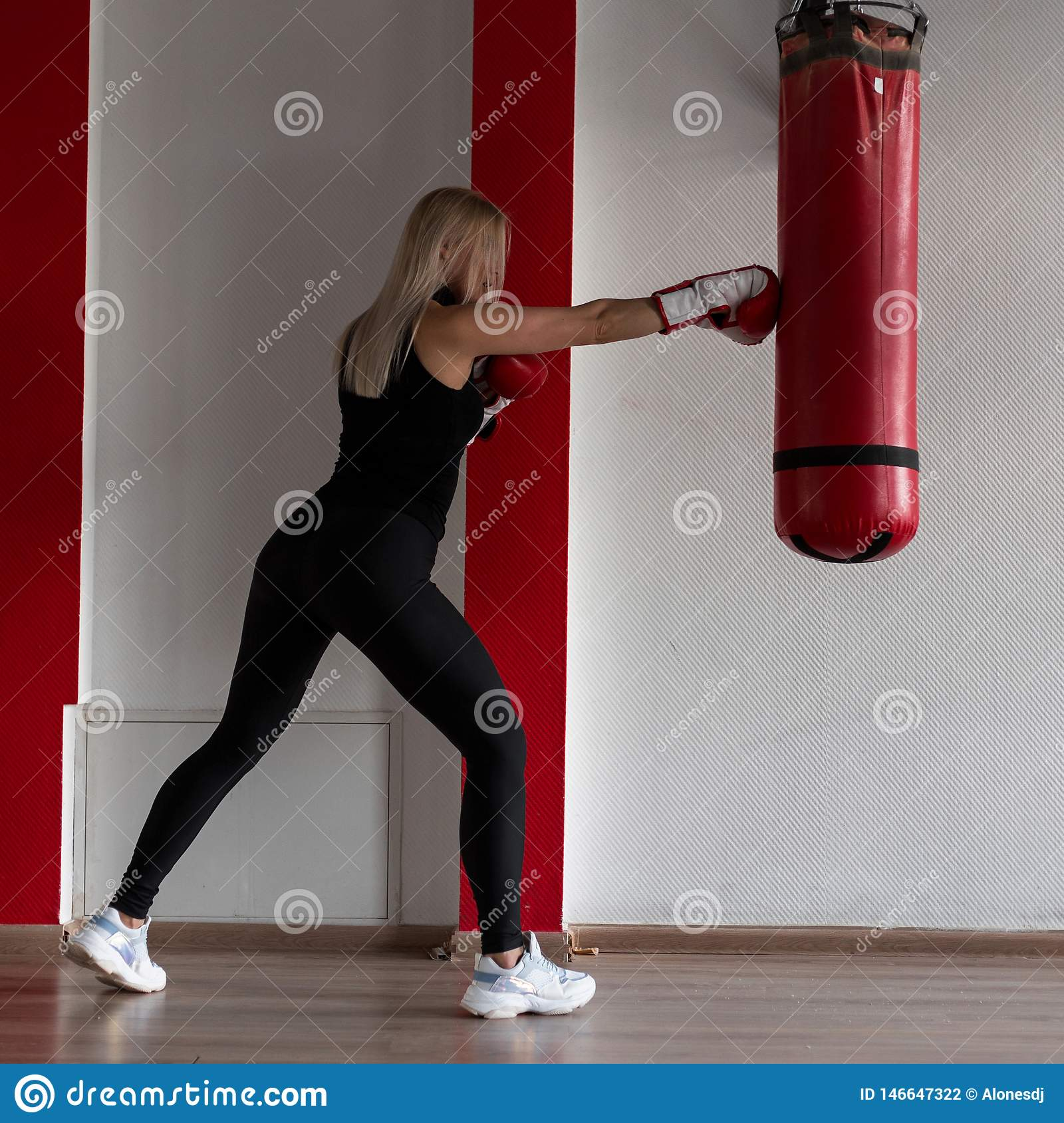 Young woman in black sportswear in stylish sneakers in red boxing gloves beats a punching bag in a modern gym. Girl in training