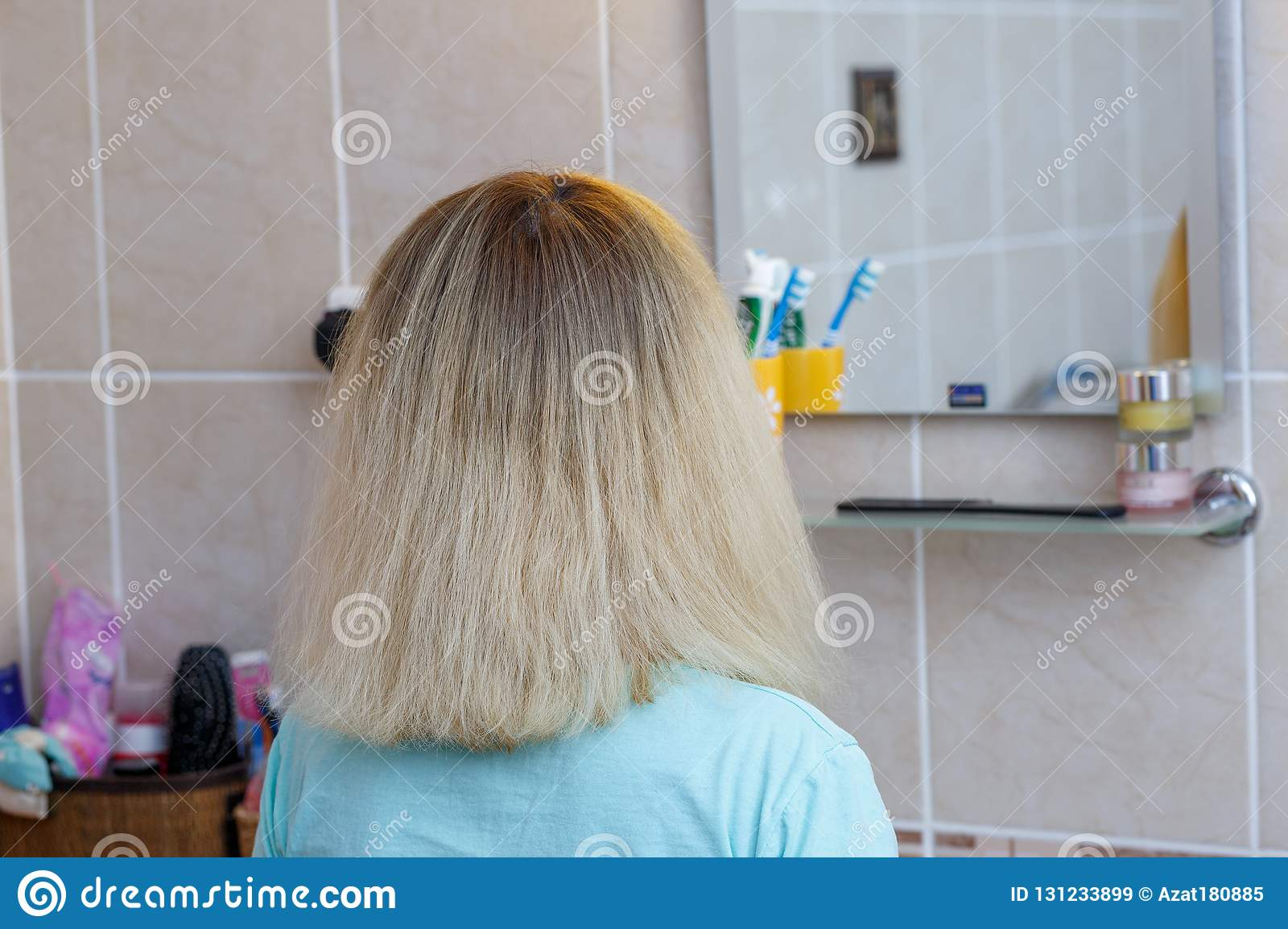 Young woman with blond hair combing her hair at home in the bathroom