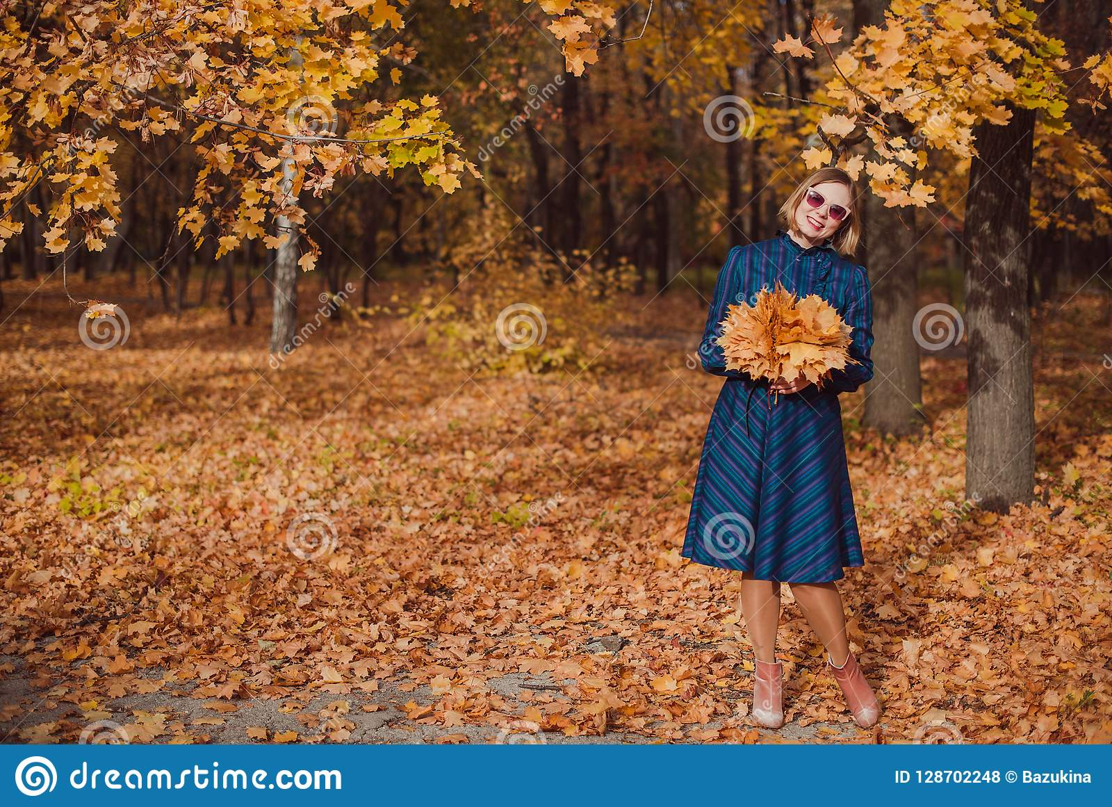 Young woman with blond hair wearing blue dress walking in autumn Park.