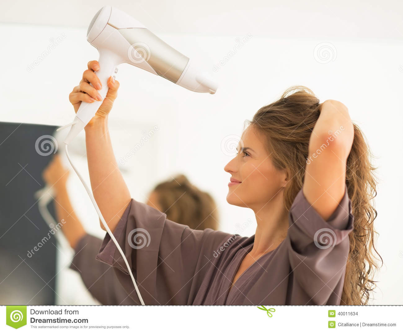 Young Woman Blow Drying Hair In Bathroom Stock Photo ...