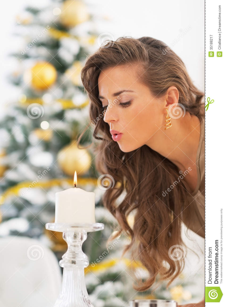 Young Woman Blowing Out Candle In Front Of Christmas Tree
