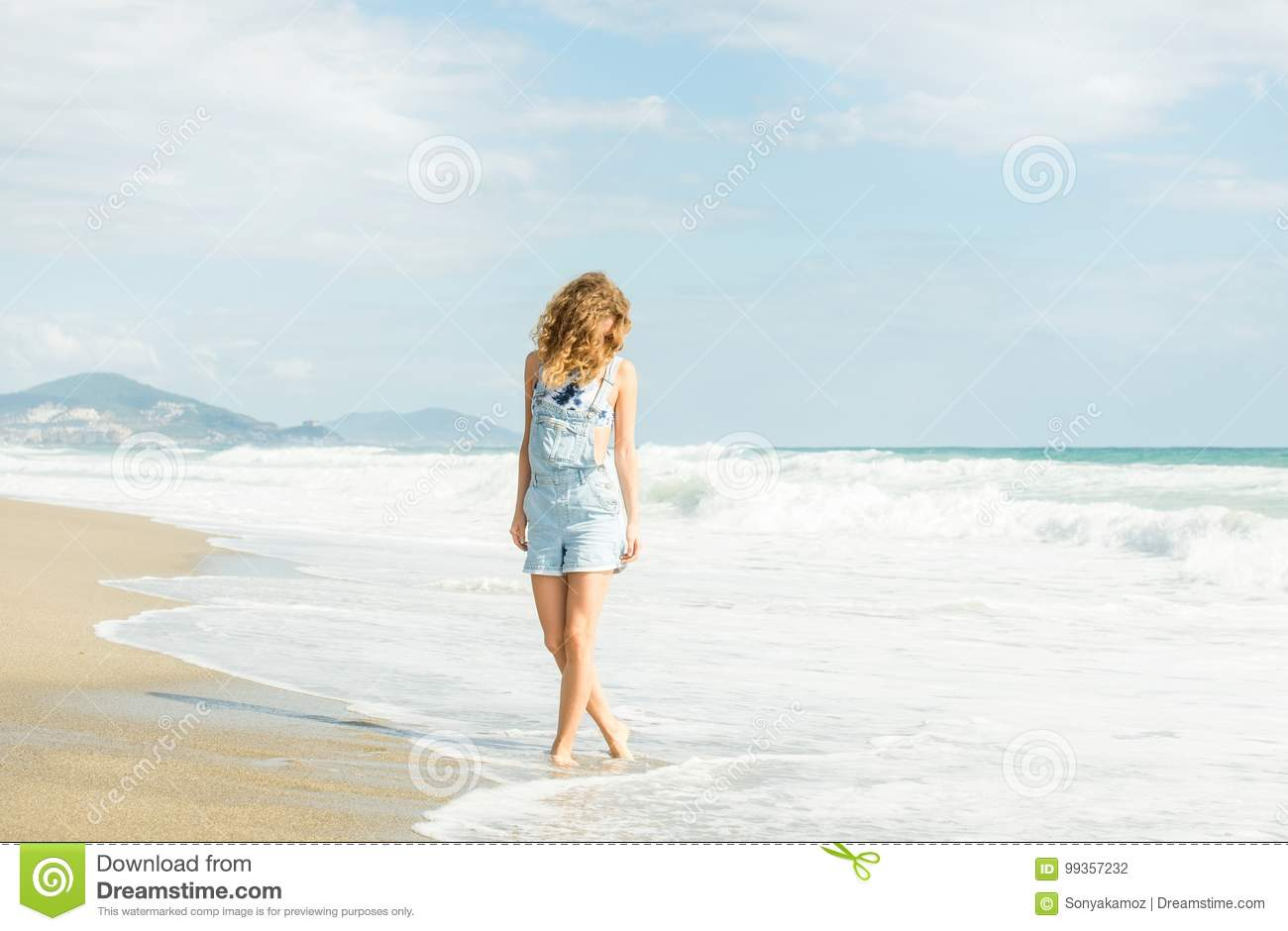 085744bfc479 Young woman in blue denim jumpsuit walking along beach and the stormy ocean  on sunny day