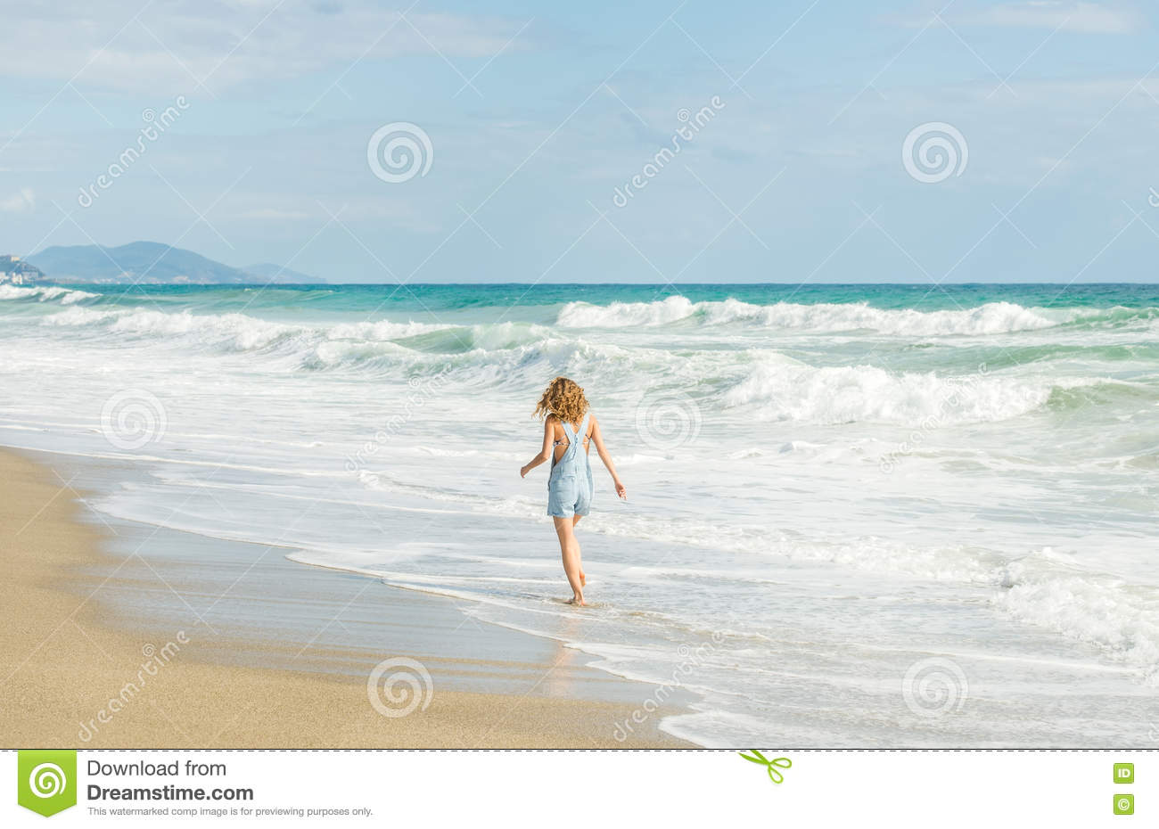 35833653c961 Young Woman In Blue Denim Jumpsuit Walking To The Sea Stock Photo ...