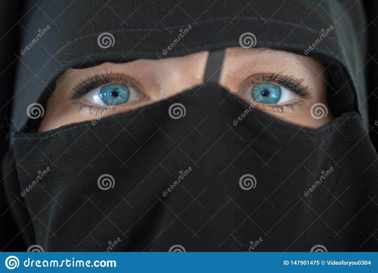 Young woman with blue eyes in black nibe close up. The girl in the burqa. People religious lifestyle concept