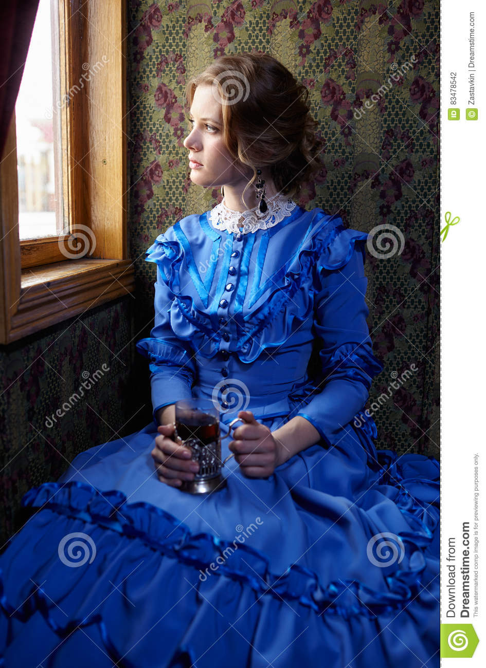 Young woman in blue vintage dress sitting in coupe of retro rai