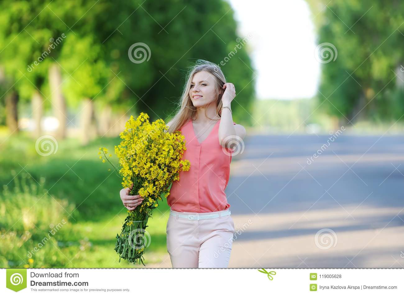 Young woman with bouquet of yellow colors walks on the country road