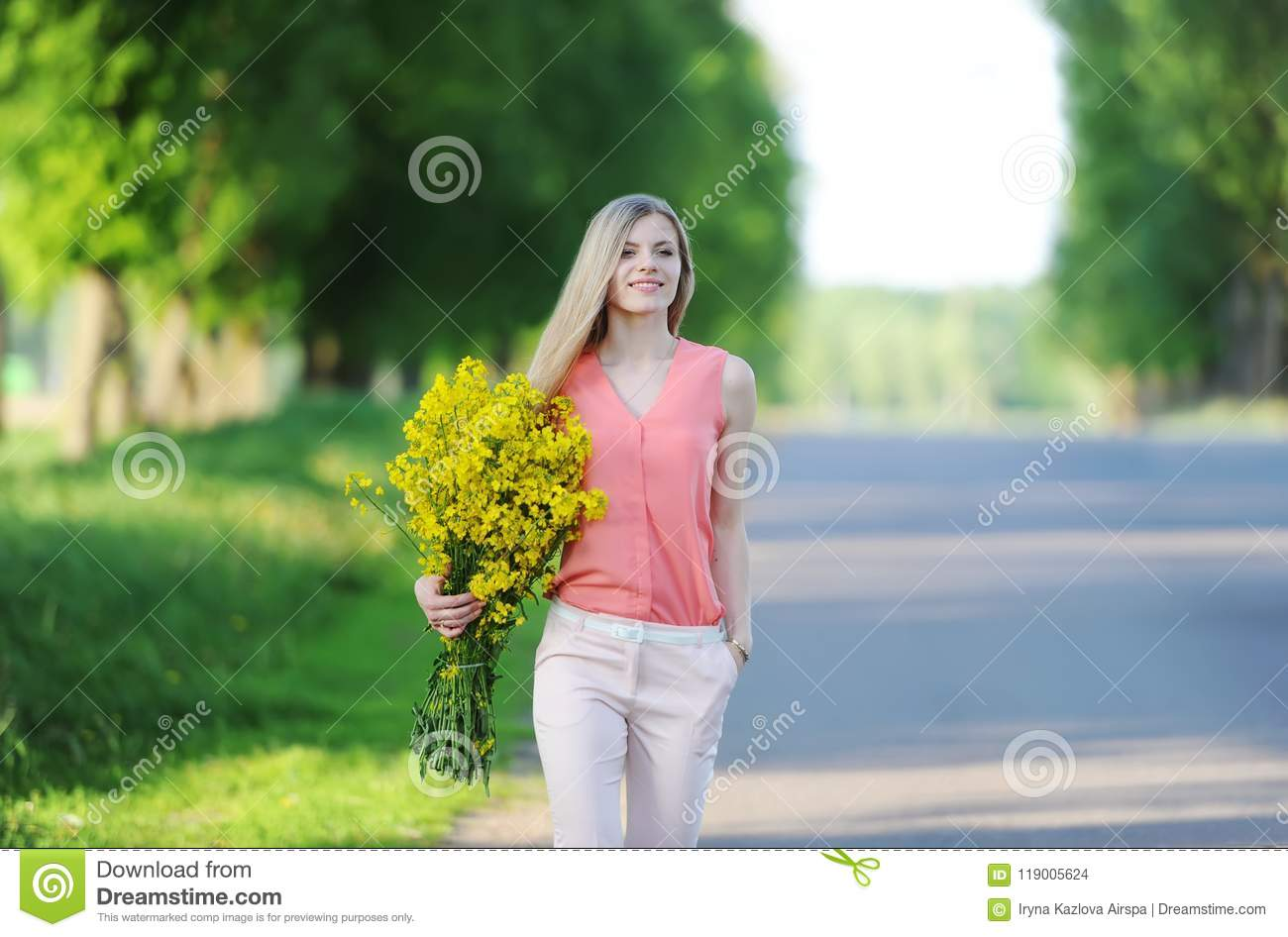 Young woman with bouquet of yellow colors walks outdoors