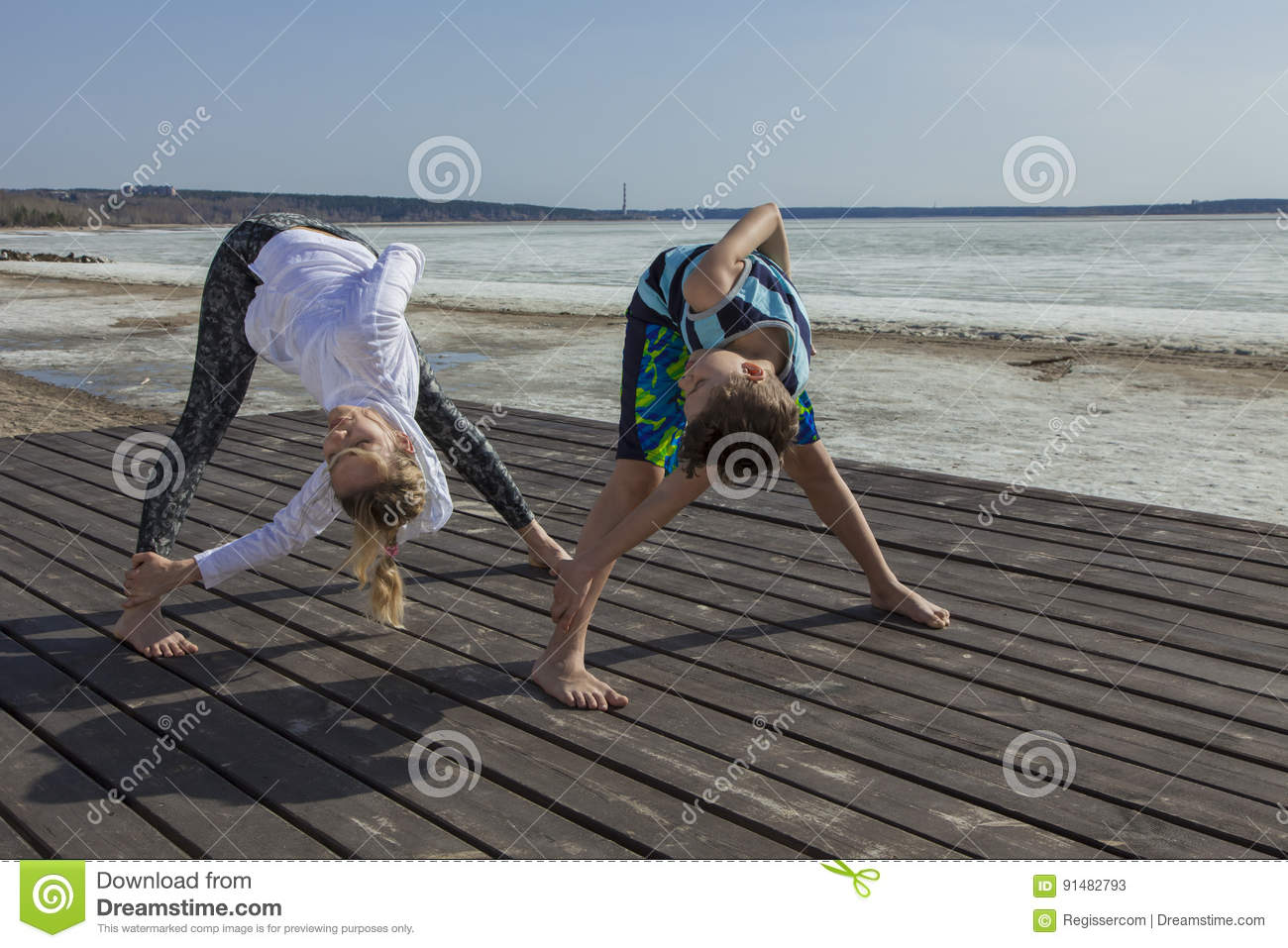 Young Woman And Boy Doing Wide Legged Forward Bend, Twist ...