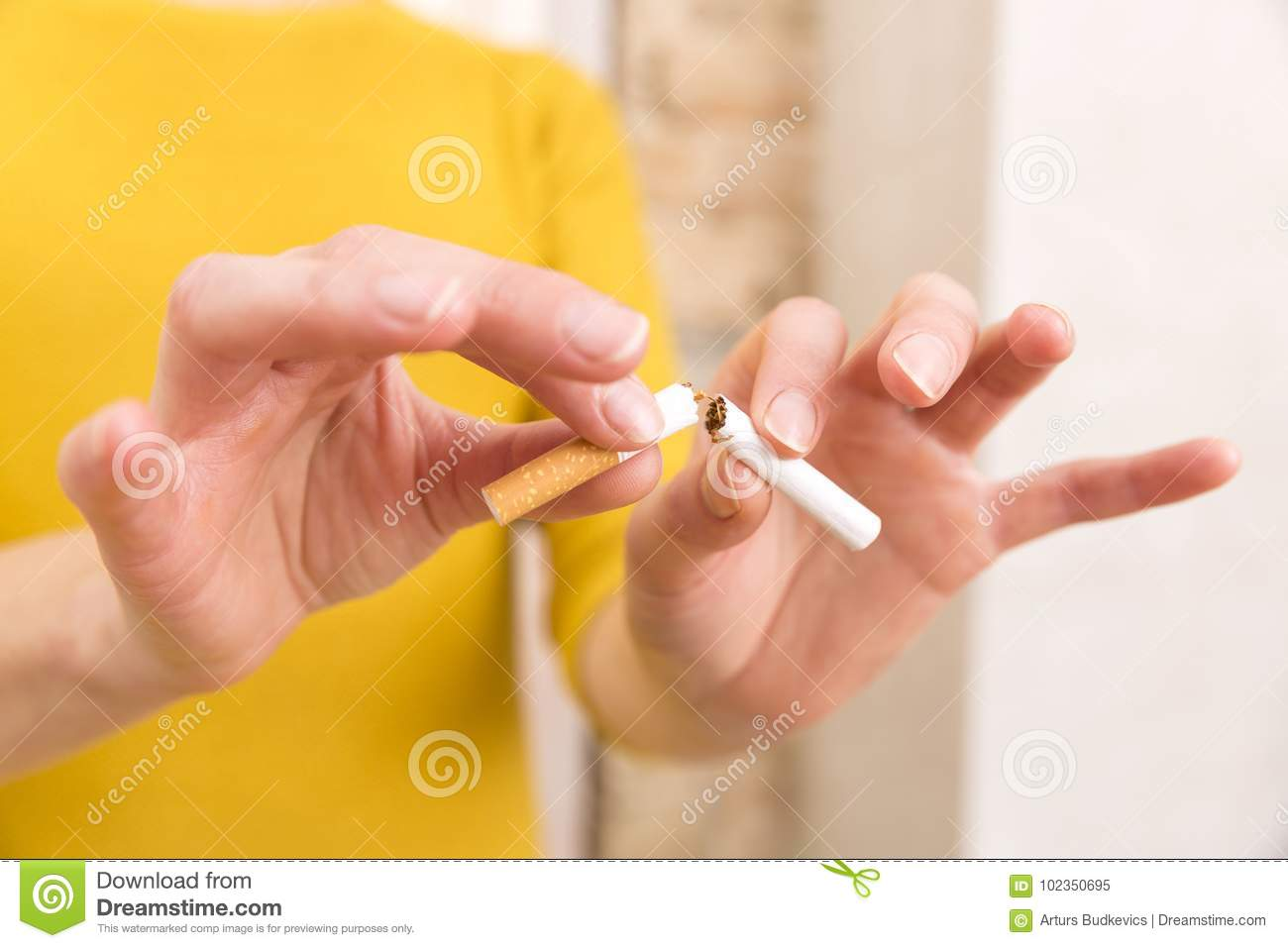 Young woman is breaking a cigarette, quit smoking concept