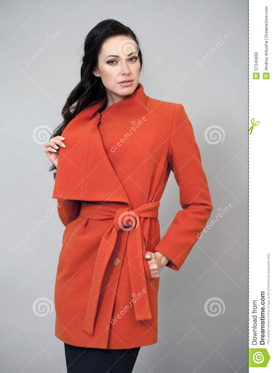 Young woman in a bright orange coat