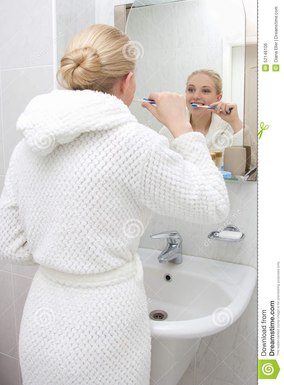 Young woman brushing teeth and looking at mirror in bathroom