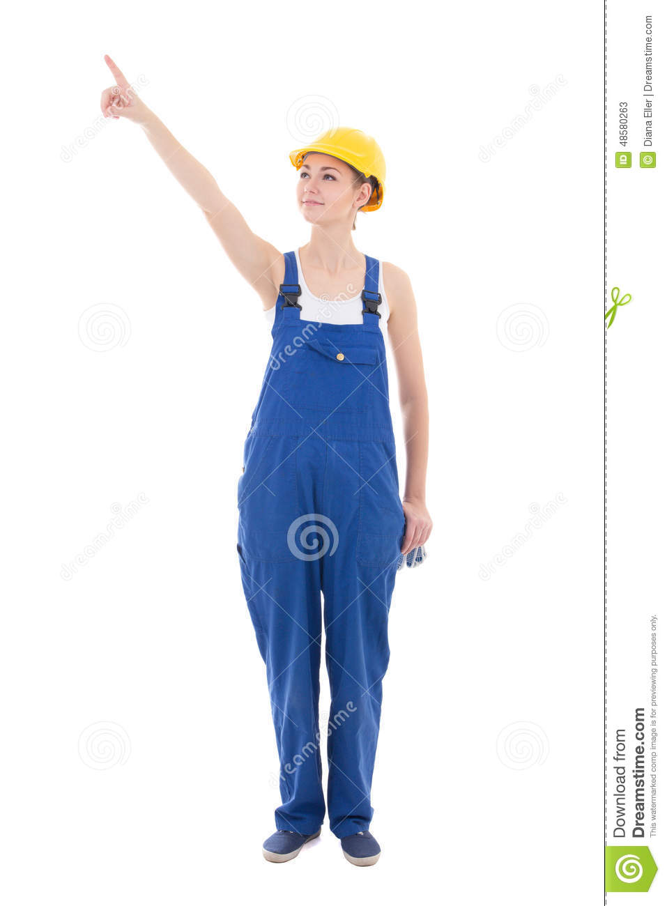 Young woman builder pointing at something isolated on white