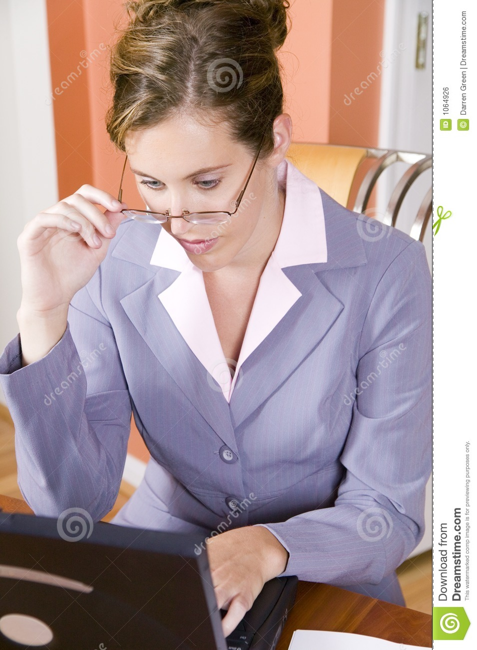 Young woman in business suit working from home