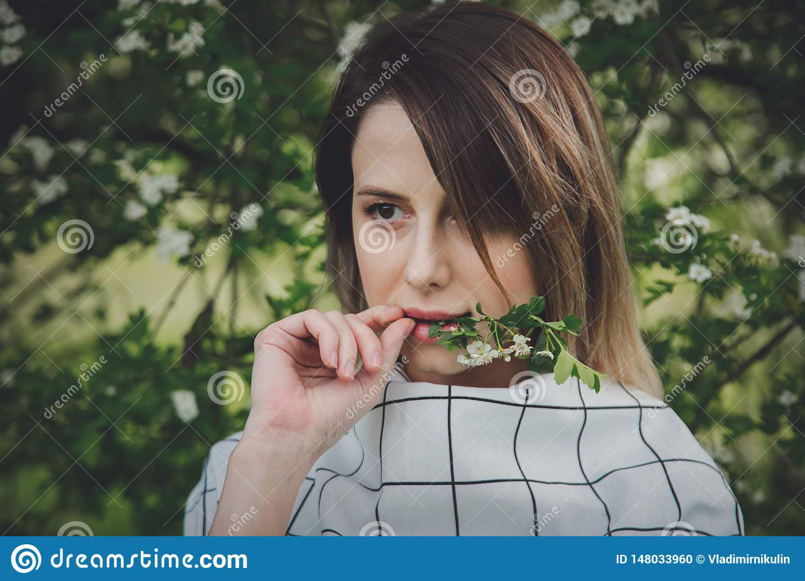 Young woman in a checkered dressstay near a flowering tree