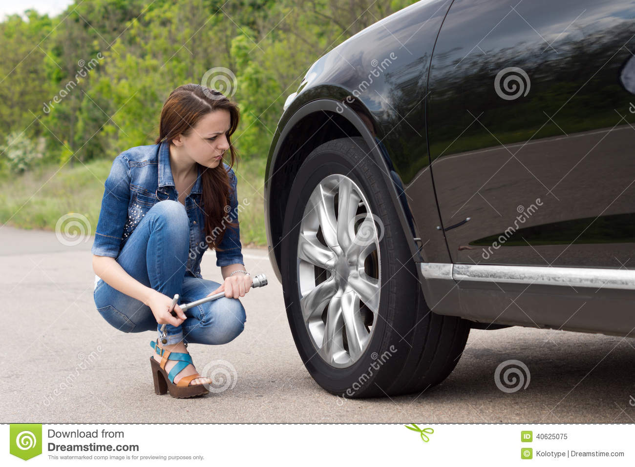 young woman checking out a flat tyre on her car stock photo image 40625075. Black Bedroom Furniture Sets. Home Design Ideas