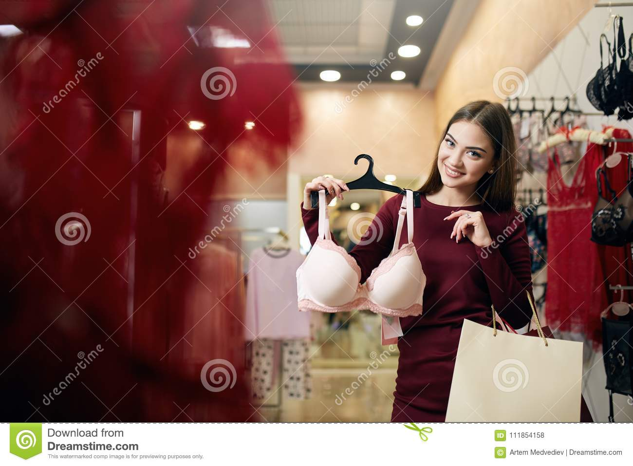 0f5343196a98a Young woman chooses brassiere among set in a boutique. Pretty girl  considers bra with shopping bags in her hand in underwear store.  Consumerism concept