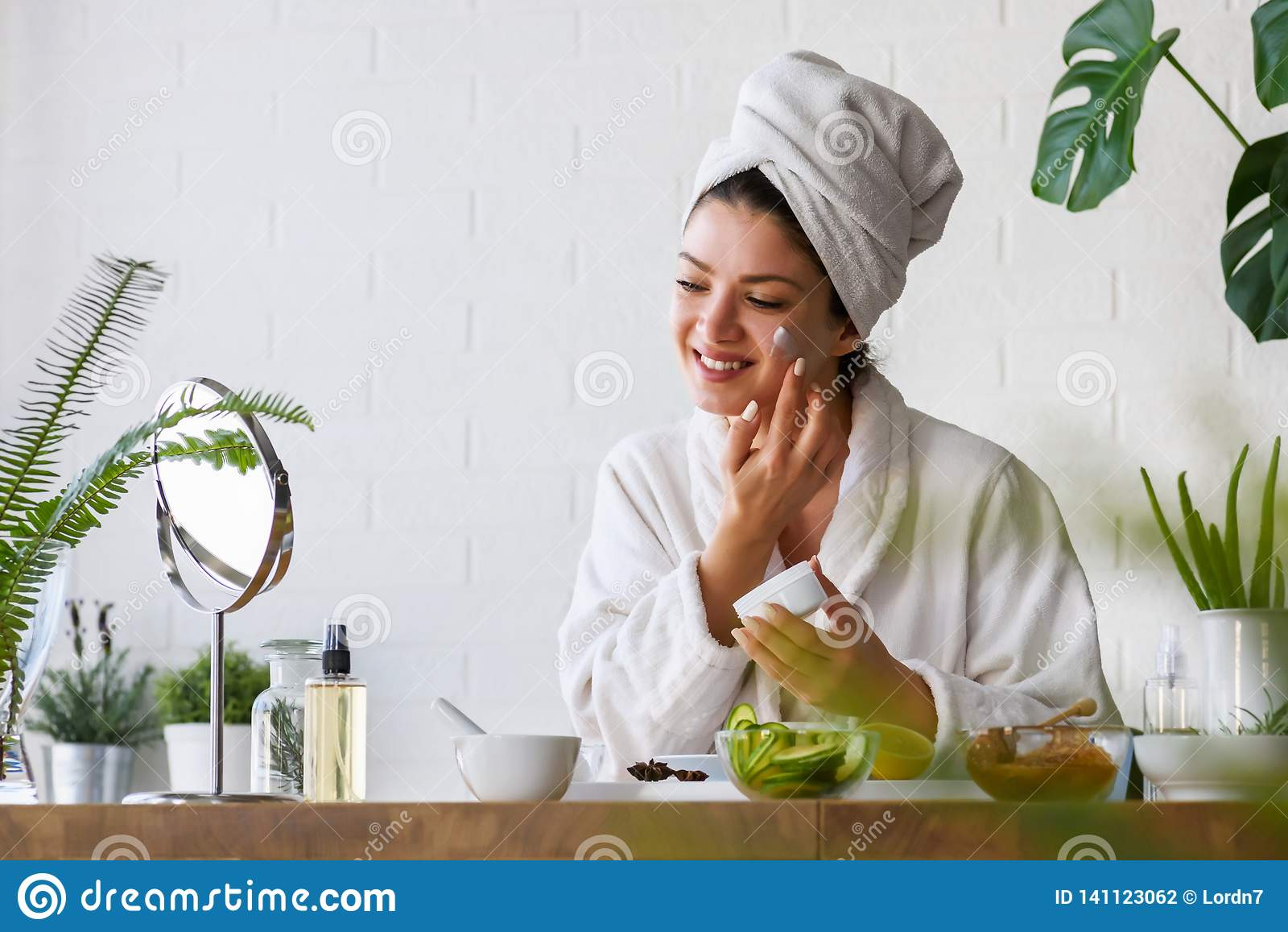 Young woman cleaning face with natural cosmetics. Clean fresh skin care.