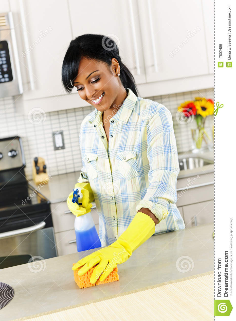 Hardworking young lady cleans the kitchen before pounding 5
