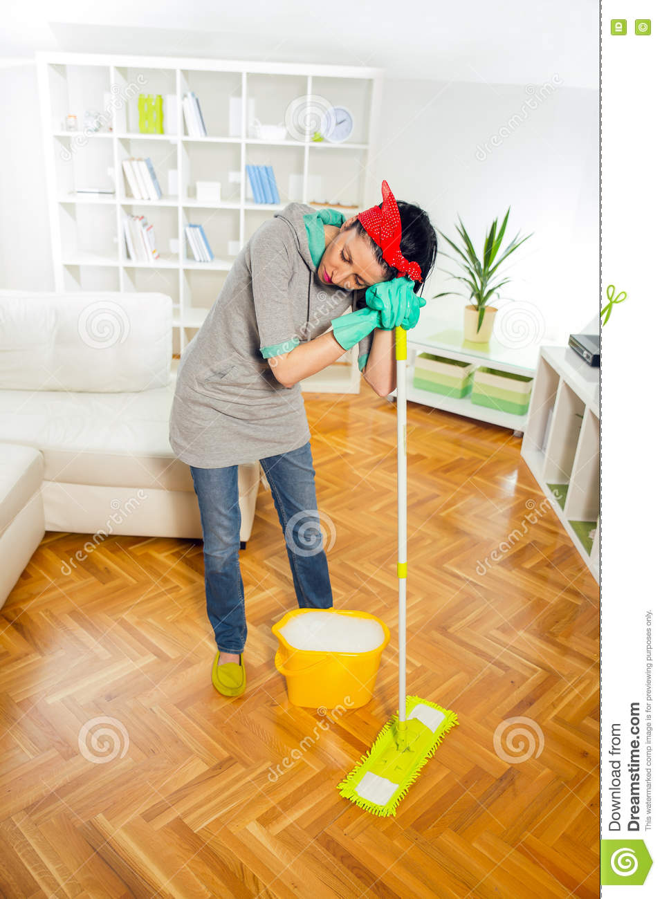 Young woman cleaning and mopping floor at home stock - One time interior house cleaning ...