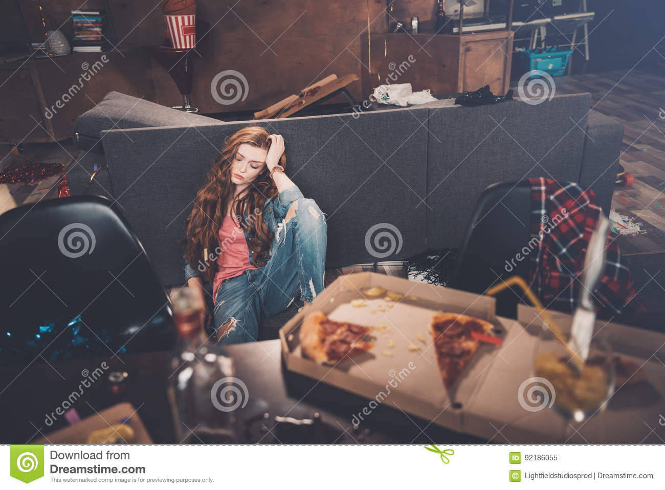 Young woman with closed eyes sitting on floor in messy room after party