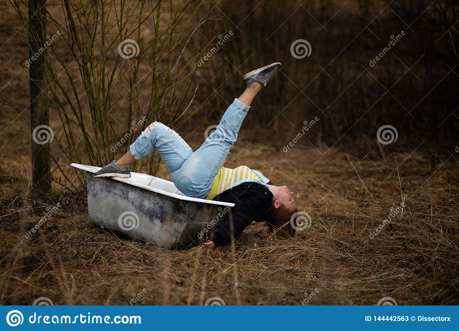 Young woman in clothes is taking an empty old bath in the middle of a forest