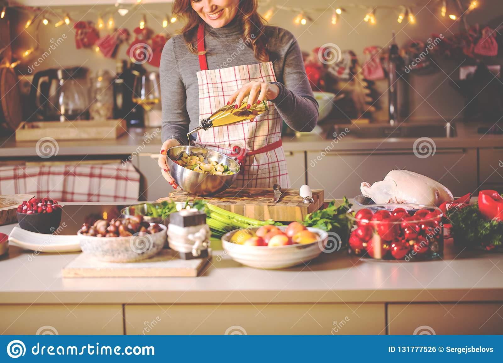Young Woman Cooking in the kitchen. Healthy Food for Christmas stuffed duck or Goose