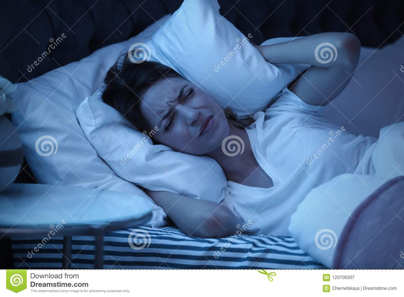Young woman covering ears with pillow while trying to sleep in bed