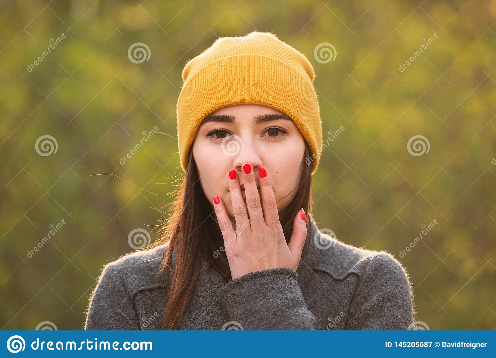 Young woman covering her mouth with her hand