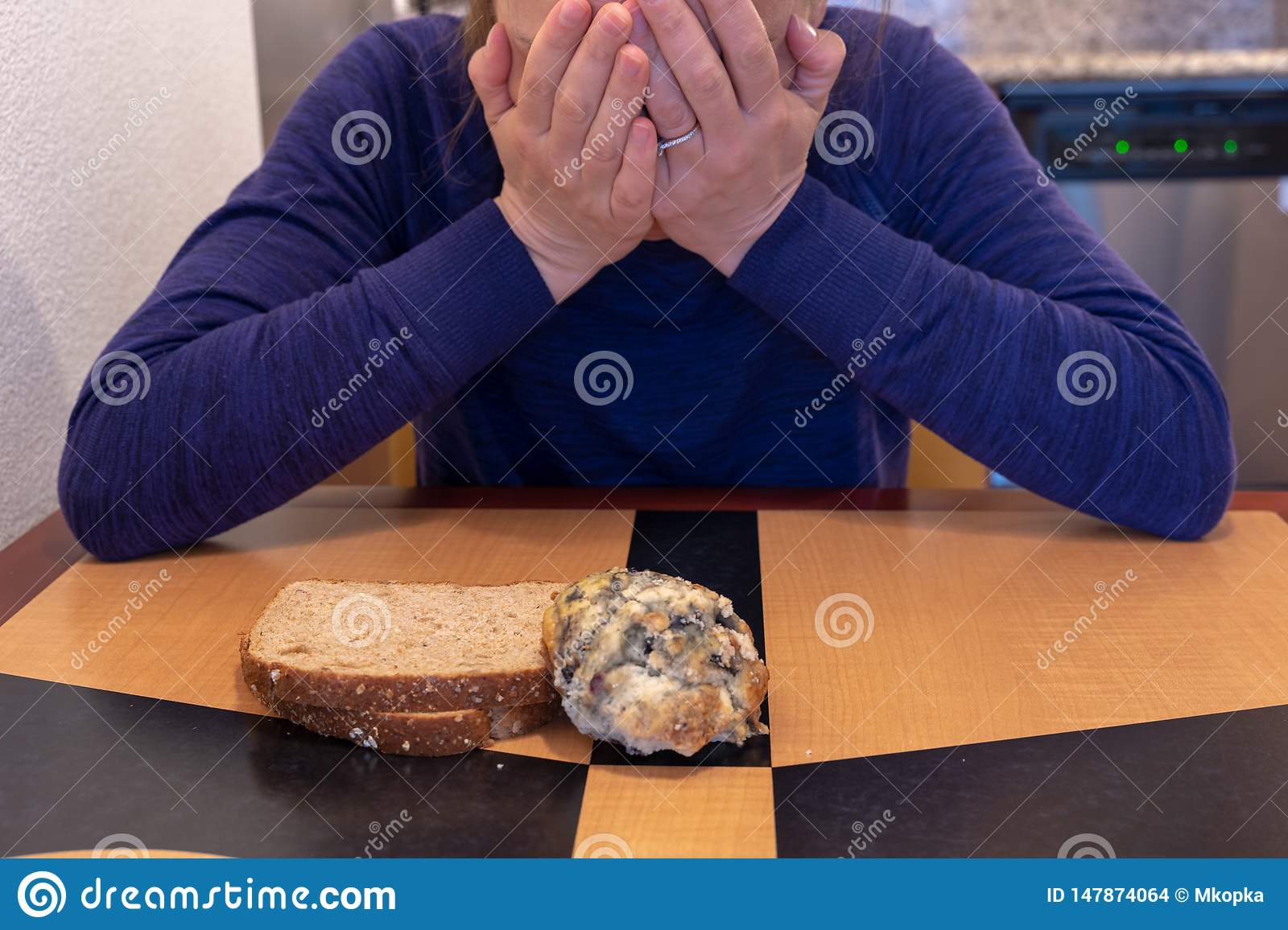 Young woman cries and buries her head and face while sitting at a kitchen table with a scone and toast. Concept for dieting and