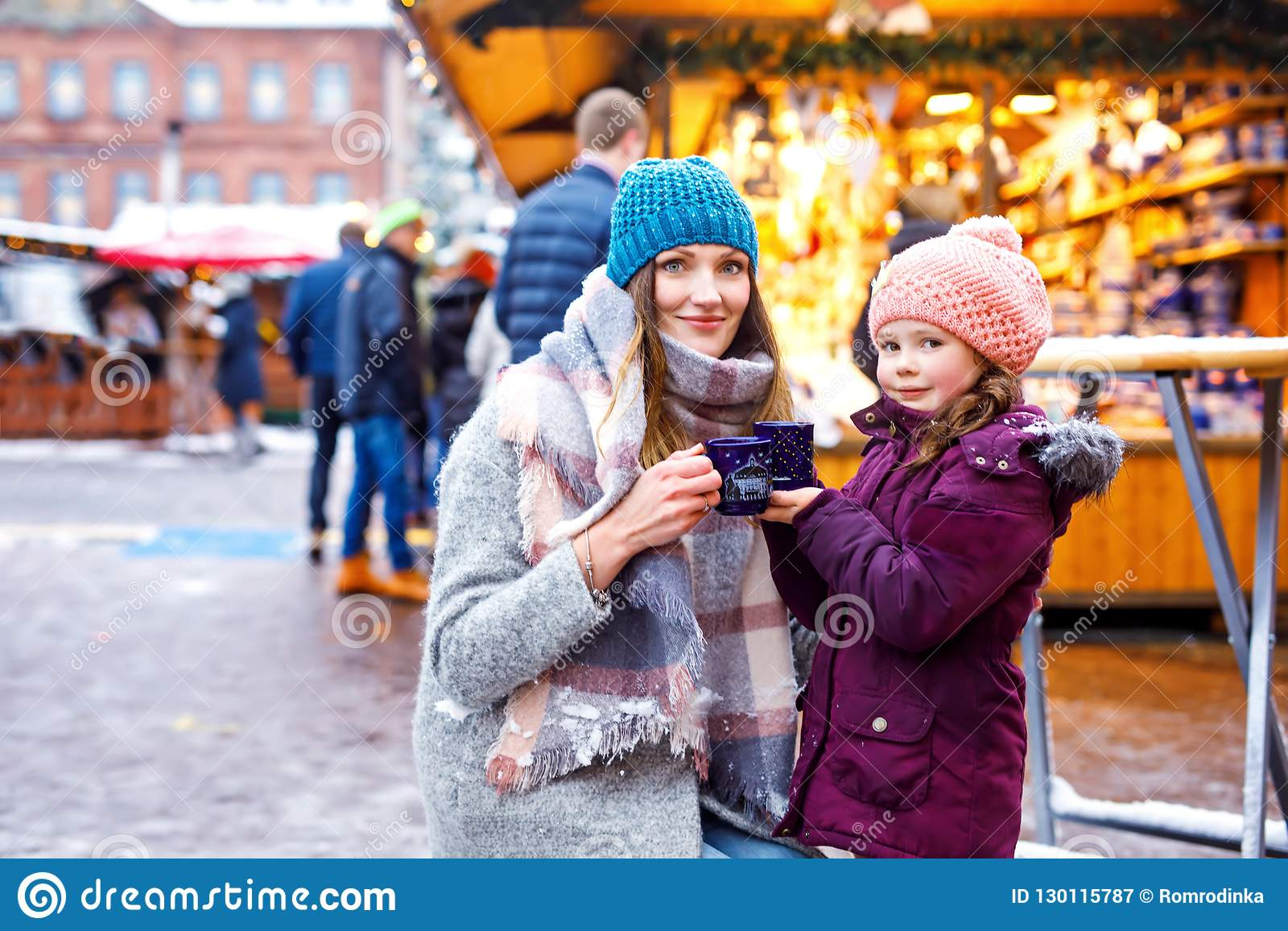Young woman and cute kid girl with cup of steaming hot chocolate or children punch