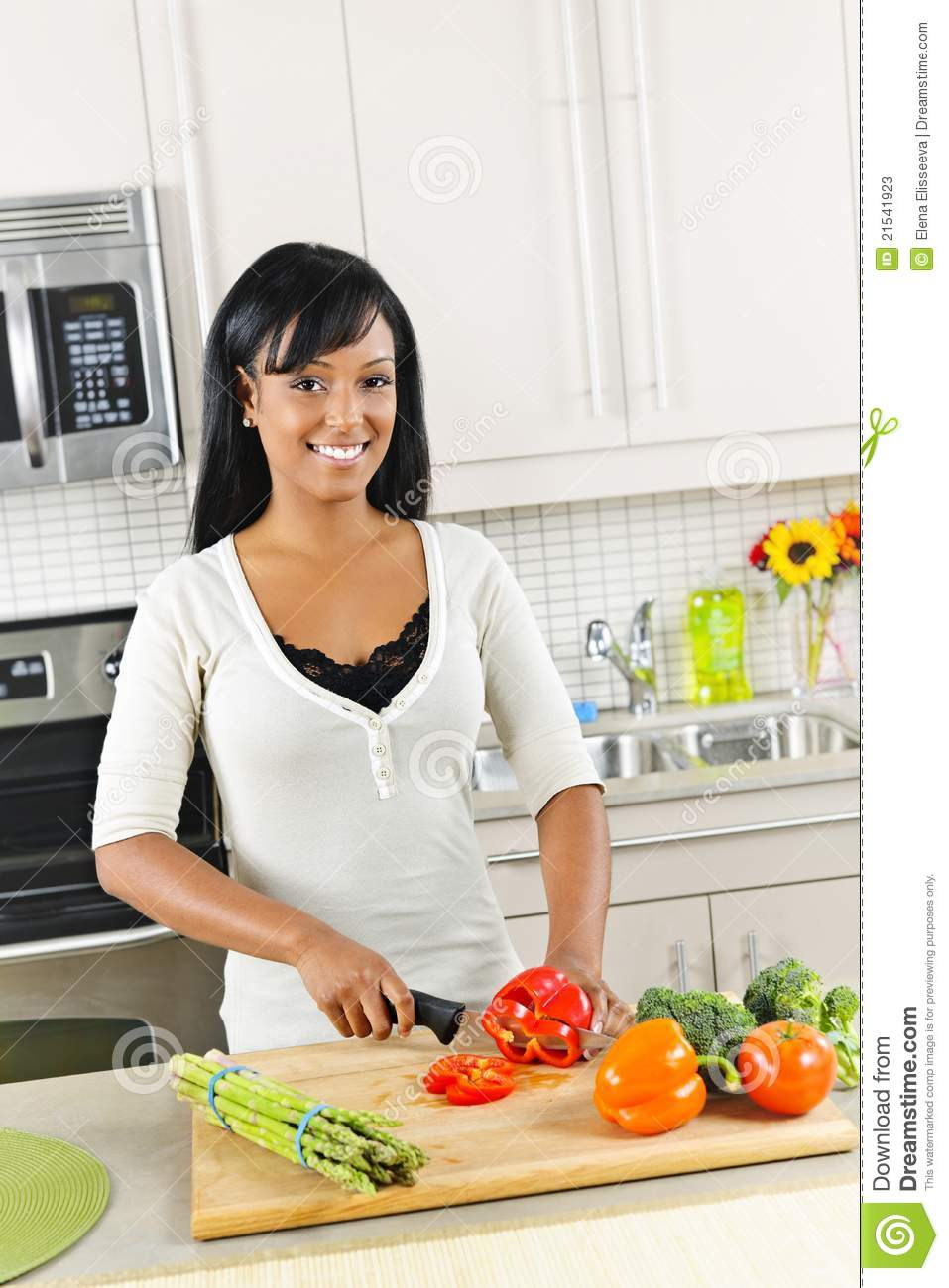 Young Woman Cutting Vegetables In Kitchen Stock Image