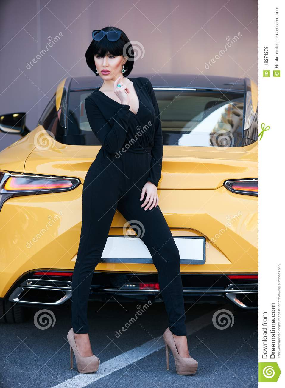 Young woman with dark hair in black bodysuit and sunglasses posing near  supercar. Portrait of a Beautiful brunette woman with yellow sport car 8be8debbb