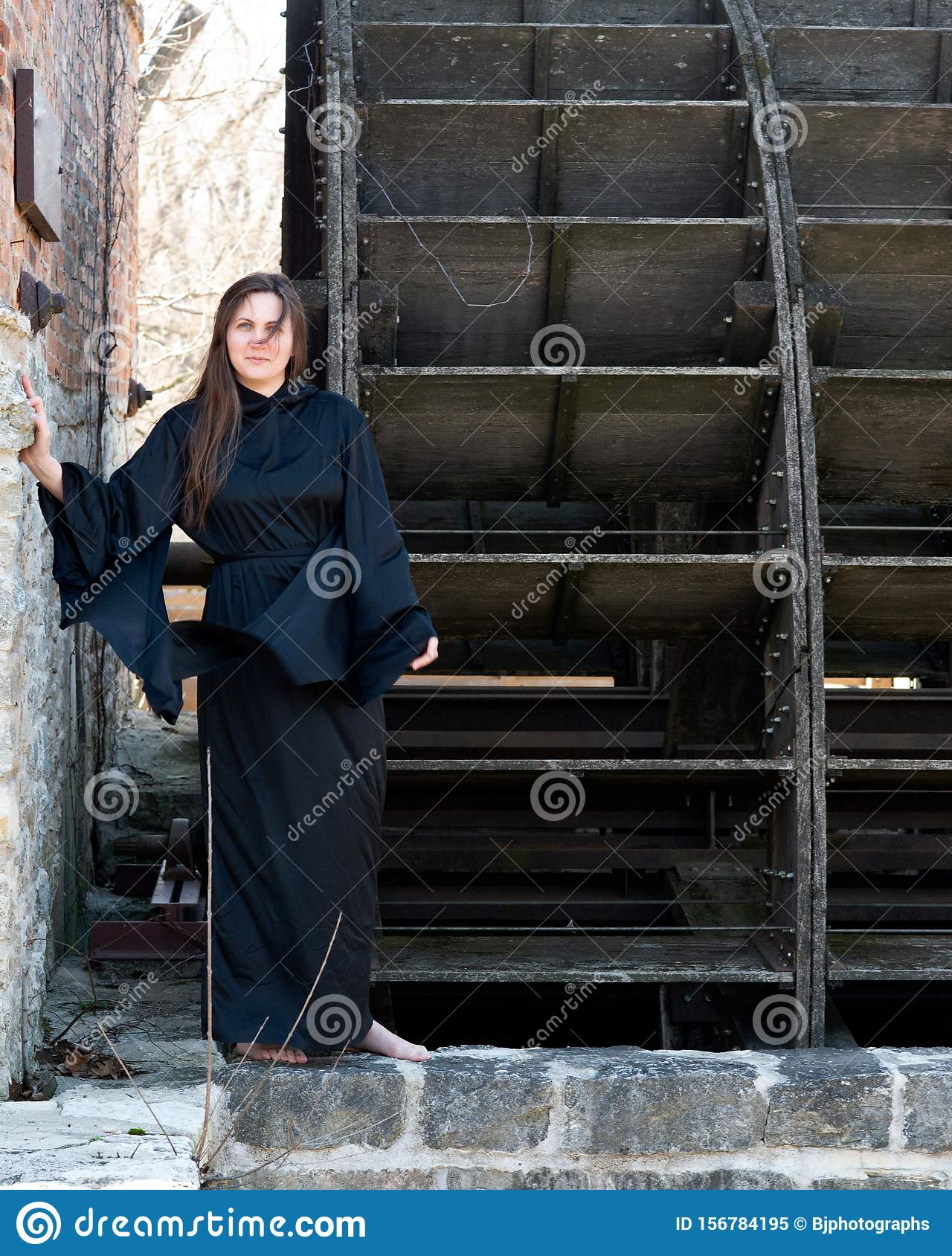 Young Woman With Dark Long Hair In Black Robes In Front Of An Old Wooden Water Mill Witches Halloween Concept Witchcraft Stock Image Image Of Fantasy Concept 156784195