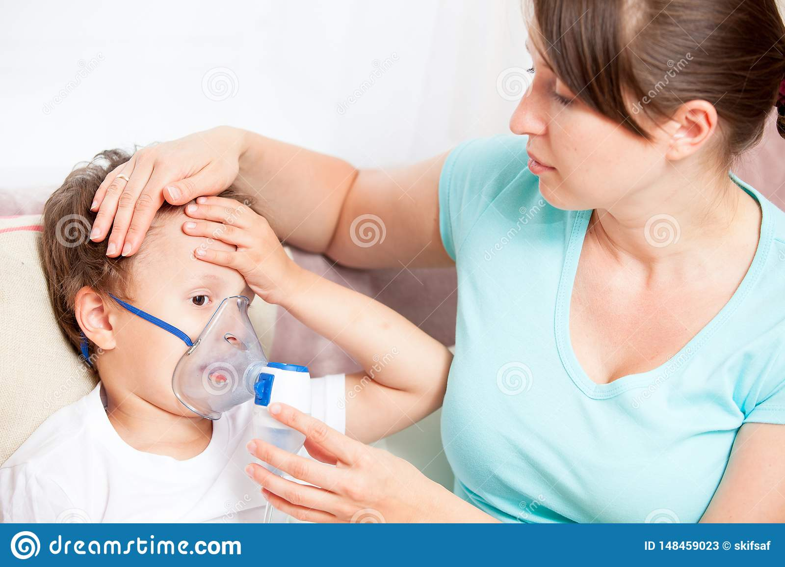 Young woman doing inhalation with a nebulizer son