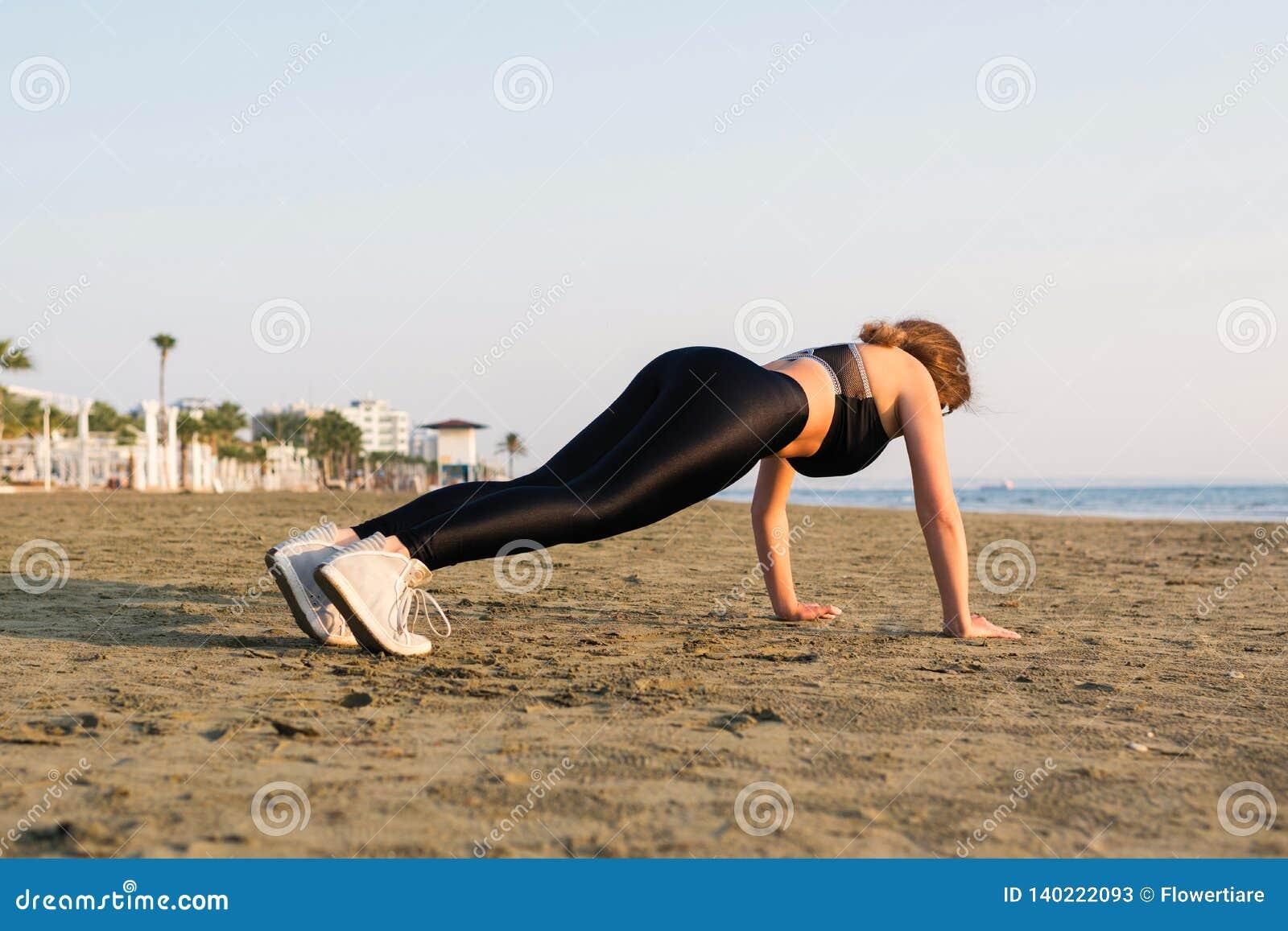 Young woman doing pushups on beach.