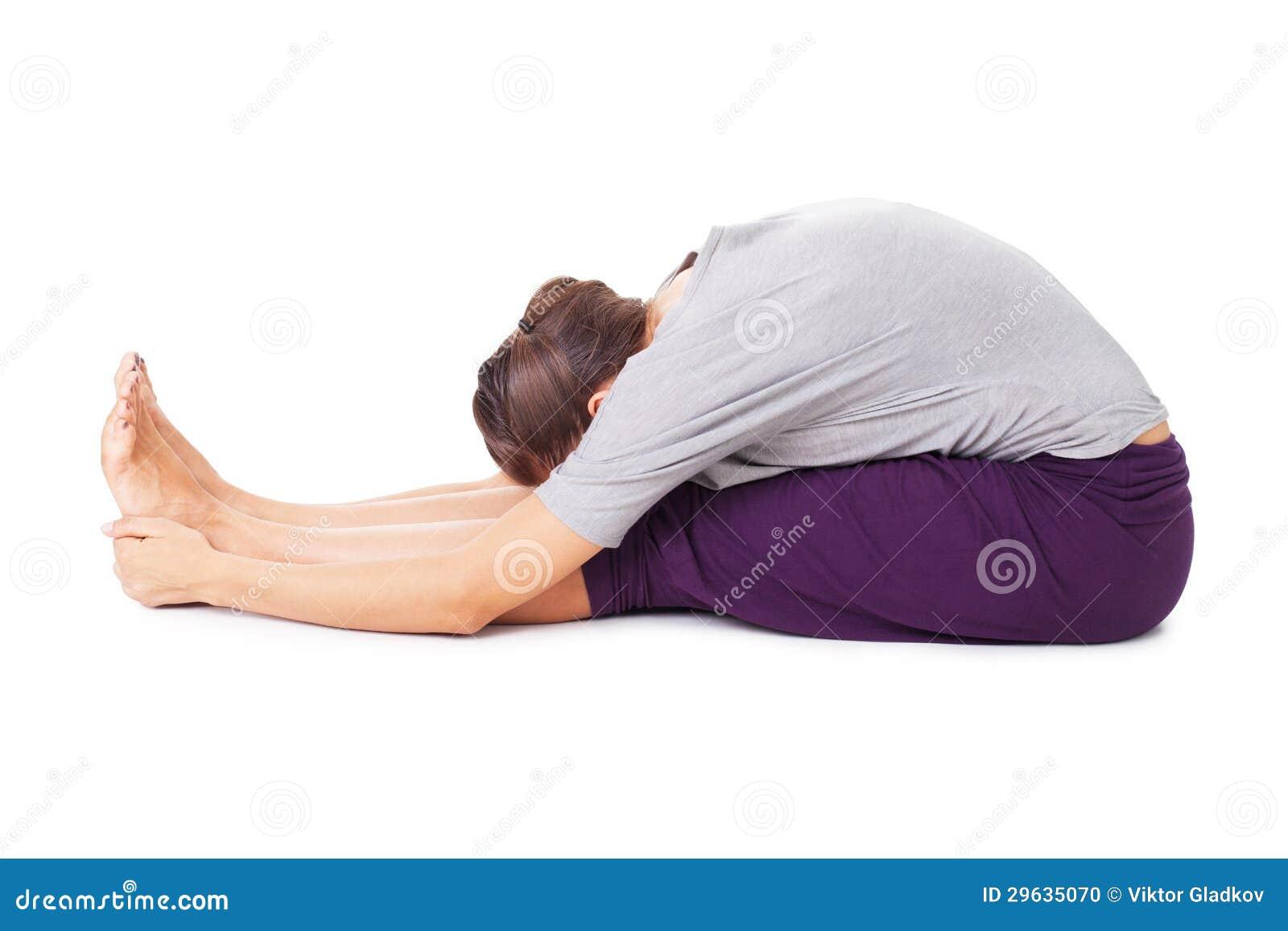 Young woman doing yoga asana seated forward bend paschimottanasana