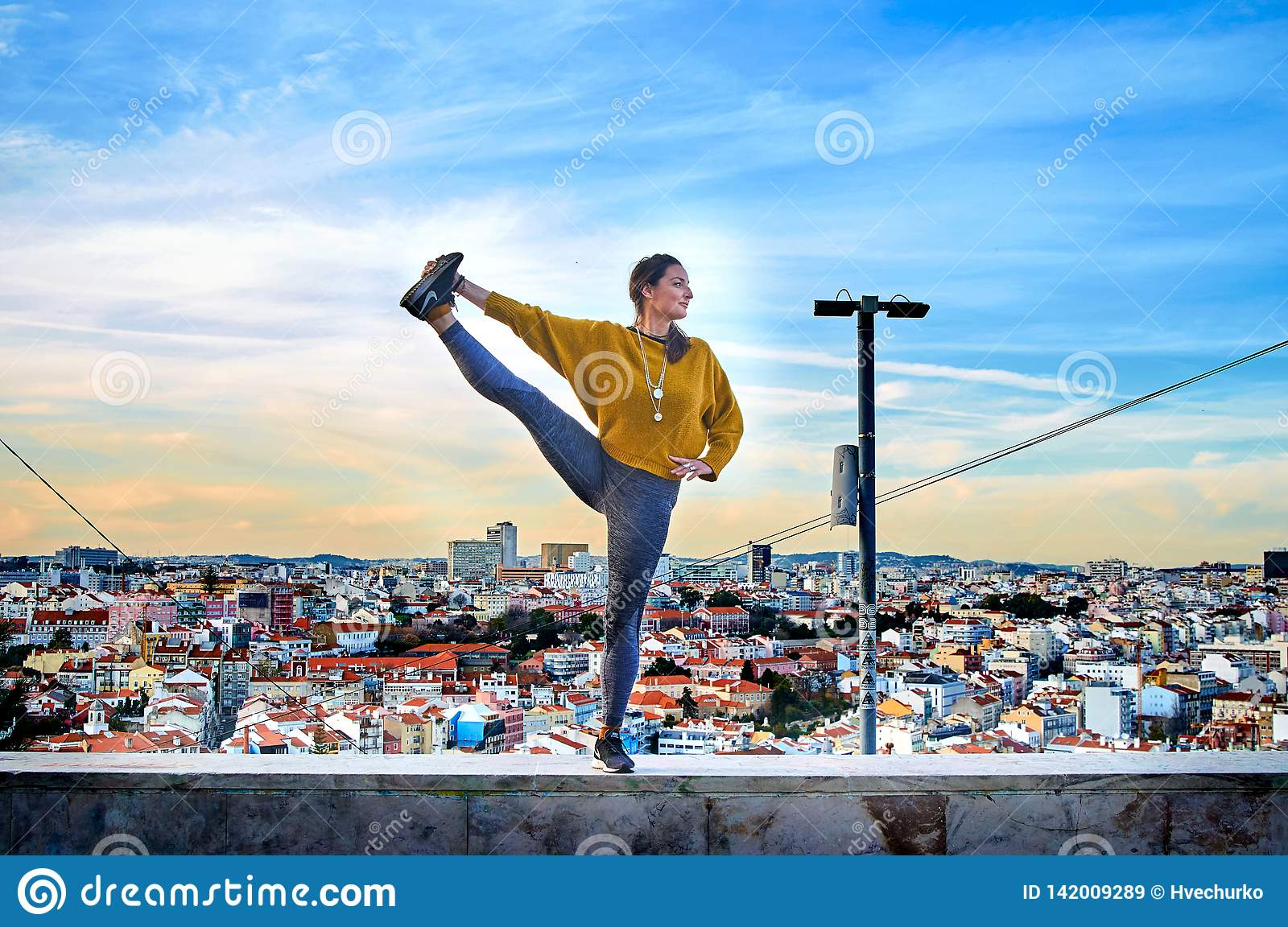 Young woman doing yoga exercise outdoors on the Lisbon city view background