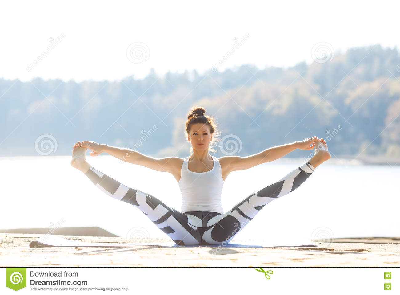 Young woman doing yoga near lake outdoors, meditation. Sport fitness and exercising in nature. Autumn sunset.