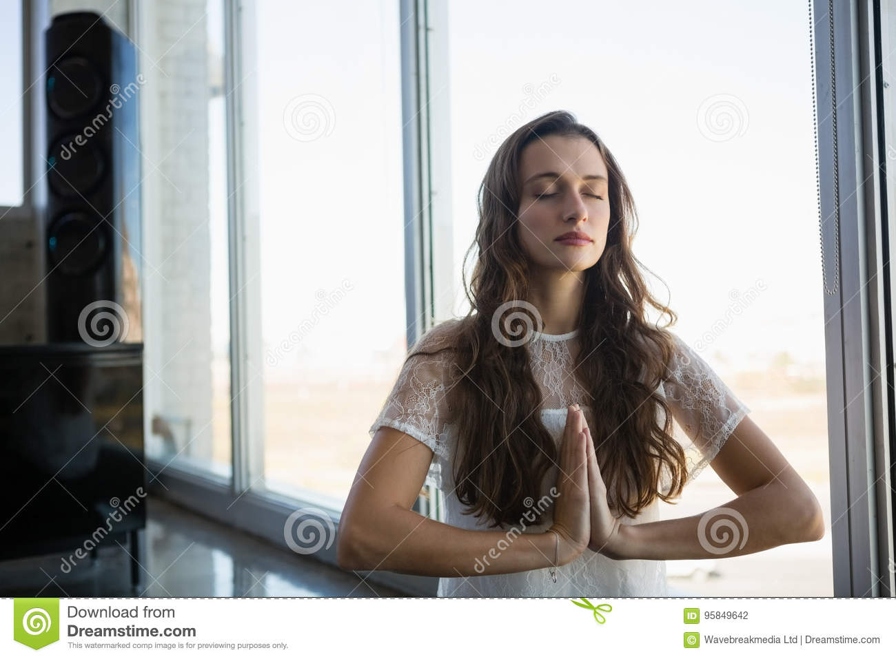 Young woman doing yoga at office