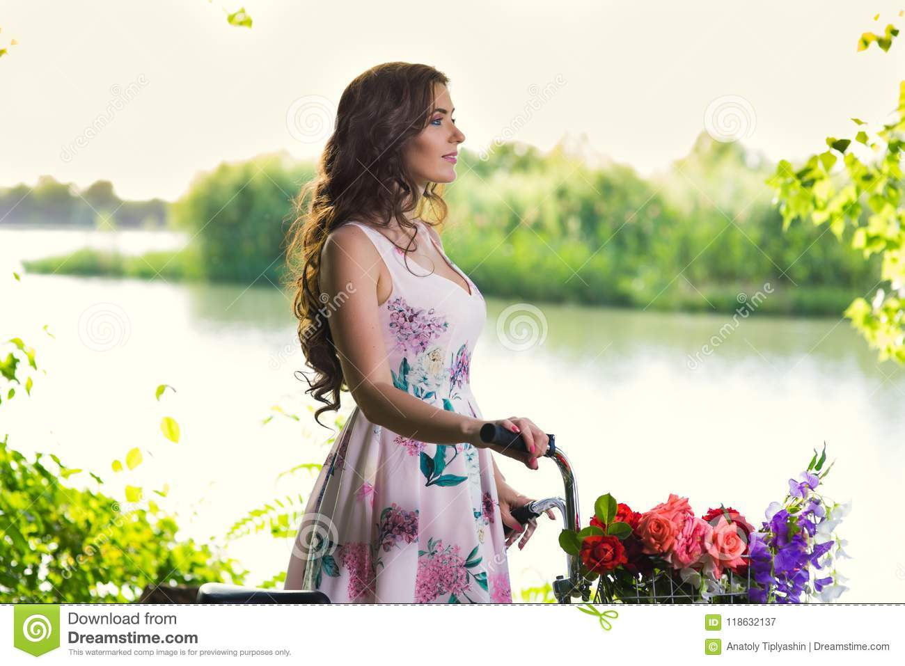 Young Woman in a Dress and Hat on a Bicycle on the Nature in th