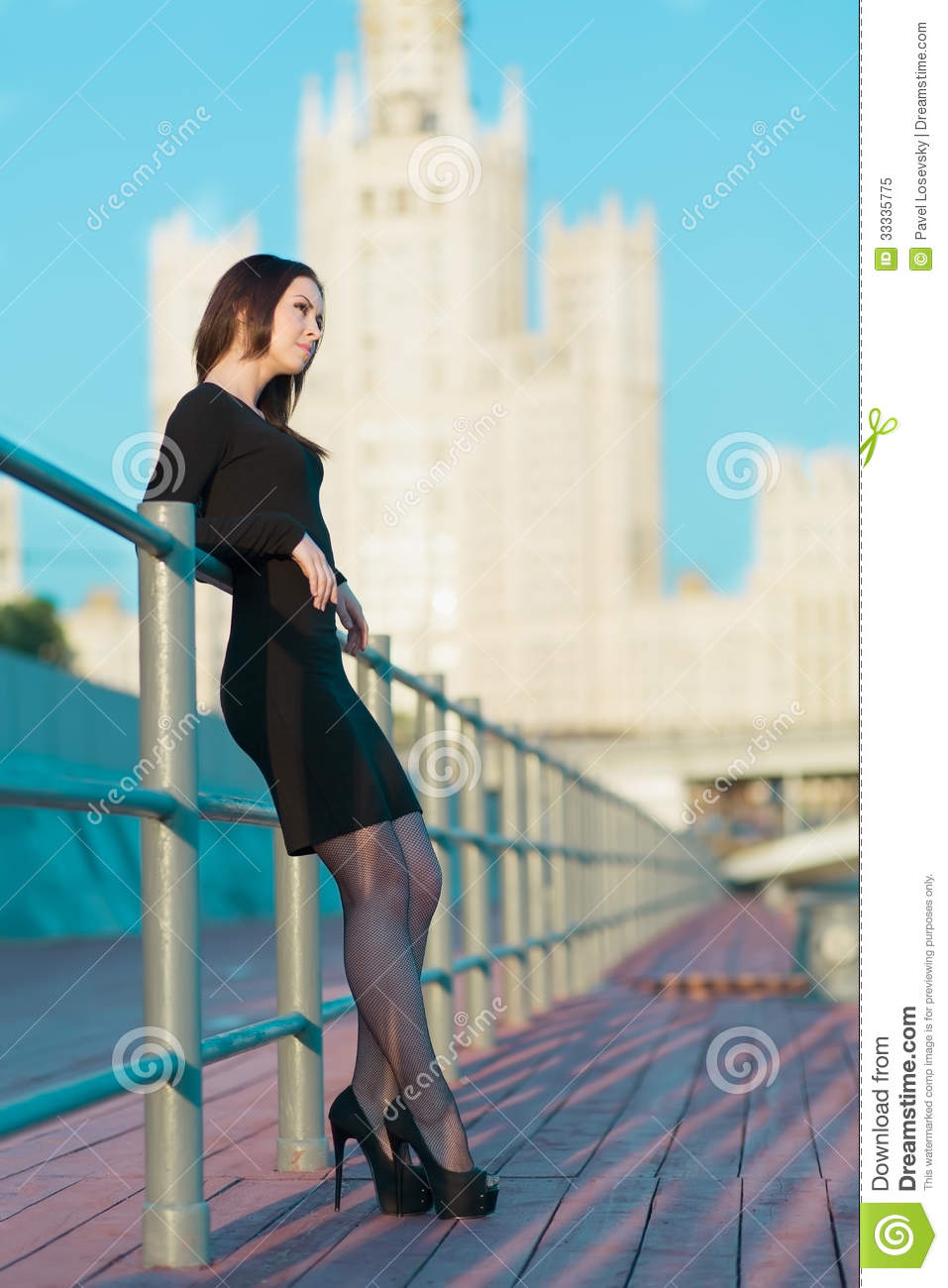 young woman in dress standing leaning on railing stock image image